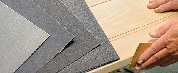 Dùng giấy nhám làm sạch, nhẵn tủ gỗ trước khi đánh Vecni